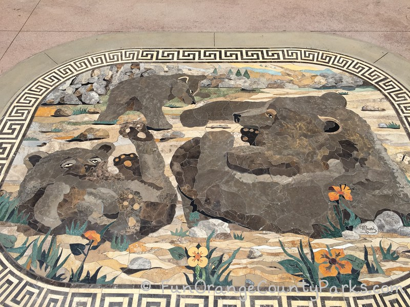 mosaic tile art set into concrete at the entrance to the playground featuring a family of bears playing in the forest and among the rocks
