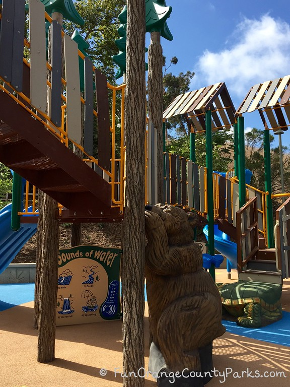 what looks like a lifesize wooden carving of a bear climbing a tree that's actually part of the playground feature of a forest-themed playground at crown valley park in laguna niguel