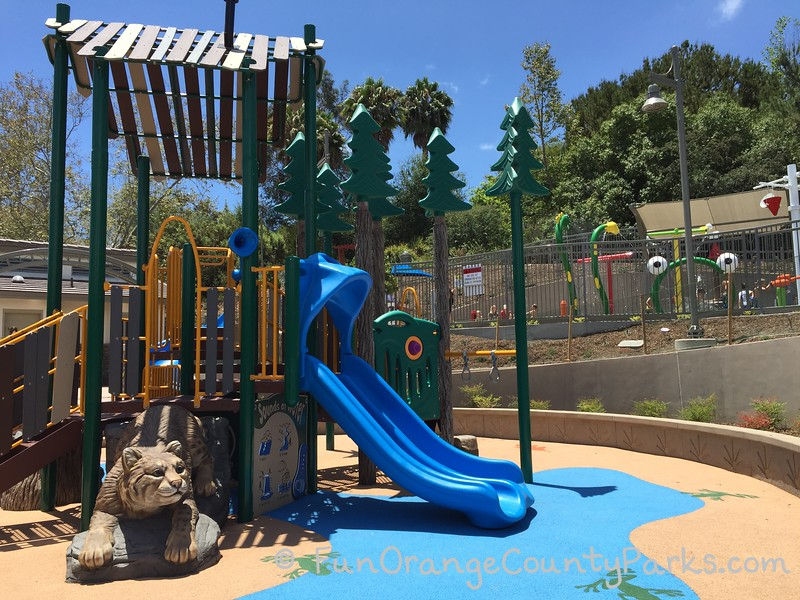 brilliant blue slide coming off small playground with what looks like pine trees and a life-size bobcat playground feature crawling from underneath the equipment -- crown valley park sprayground visible in background raised above the playground