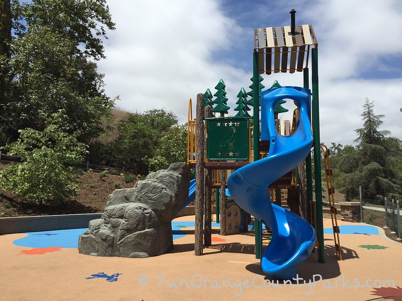 bright blue twisty slides and more rock structures to climb with another view of the playground which shows the recycled rubber surface and blue skies with clouds