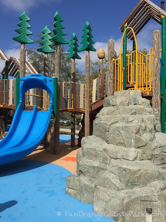 Crown Valley Park playground looks like a real forest with poles textured like pine trees and rocky outcroppings to climb alongside bright blue slides