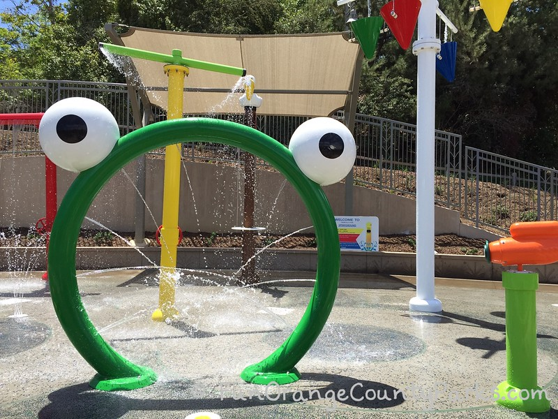 crown valley park laguna niguel splash pad with a bright metal green arch with bulgy eyes on top to help make the sprayer look like a frog with other water features partially visible