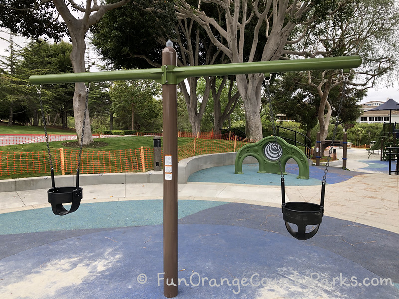 2 baby swings on blue recycled rubber play surface with trees in the background