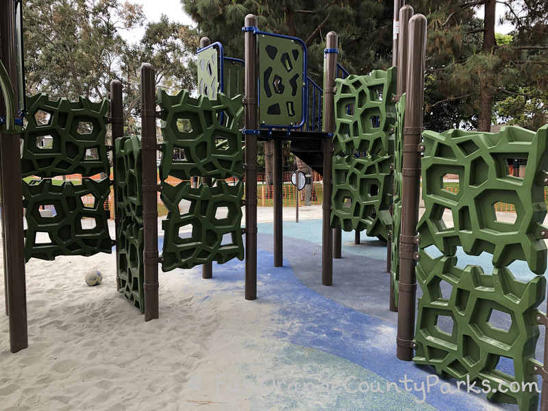 green playground panels that has holes in strange geometric shapes so children can climb across them using the holes as footholds