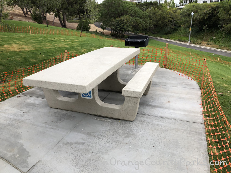 concrete picnic table with handicap sign underneath and grill at the top of a grassy hill