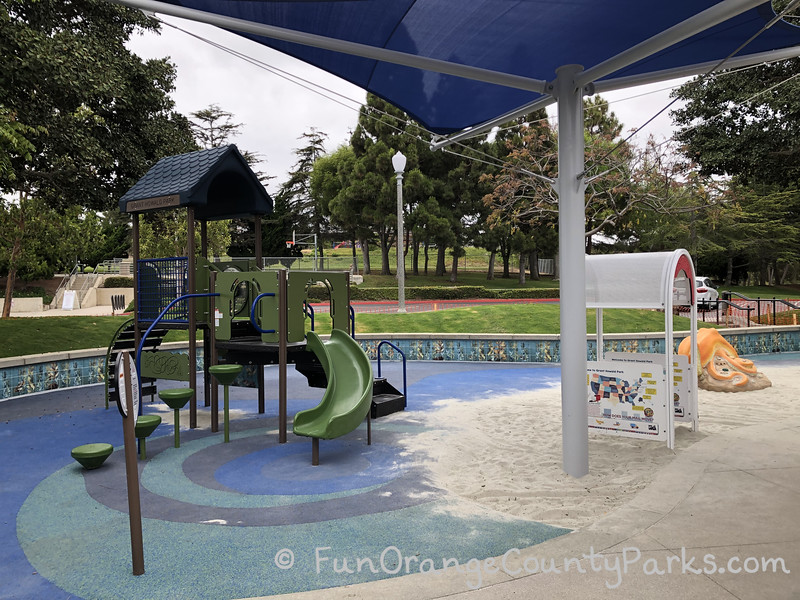 small playground with slide under blue shade cover on blue recycled rubber surface
