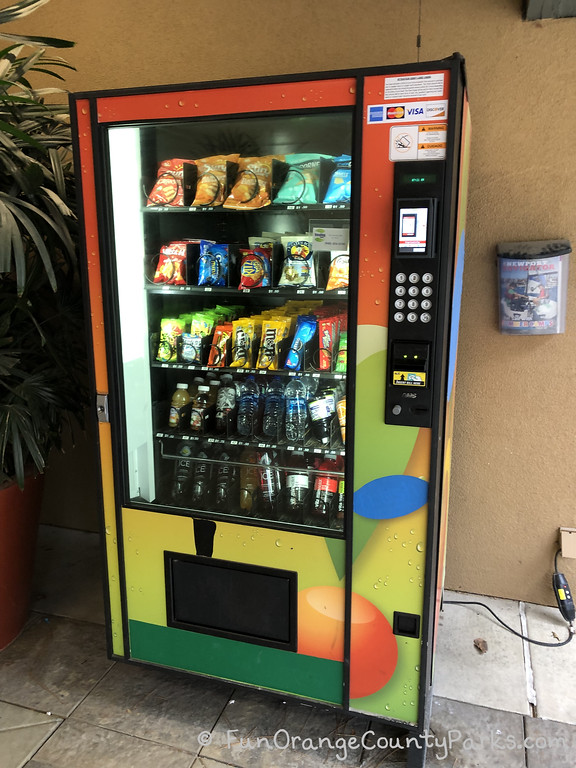 colorful vending machine stocked with snacks and water bottles