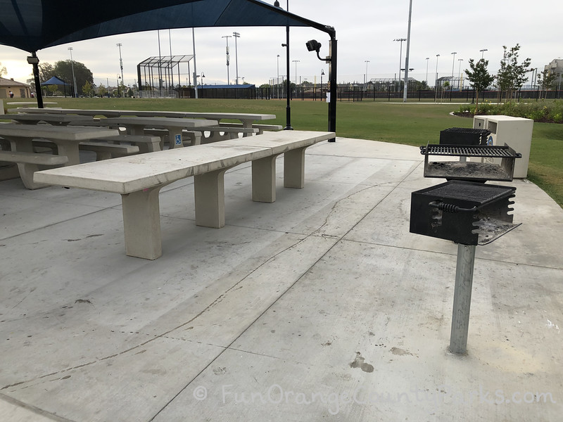picnic area with the baseball diamond in the background and three barbecue grills in the foreground with a concrete table