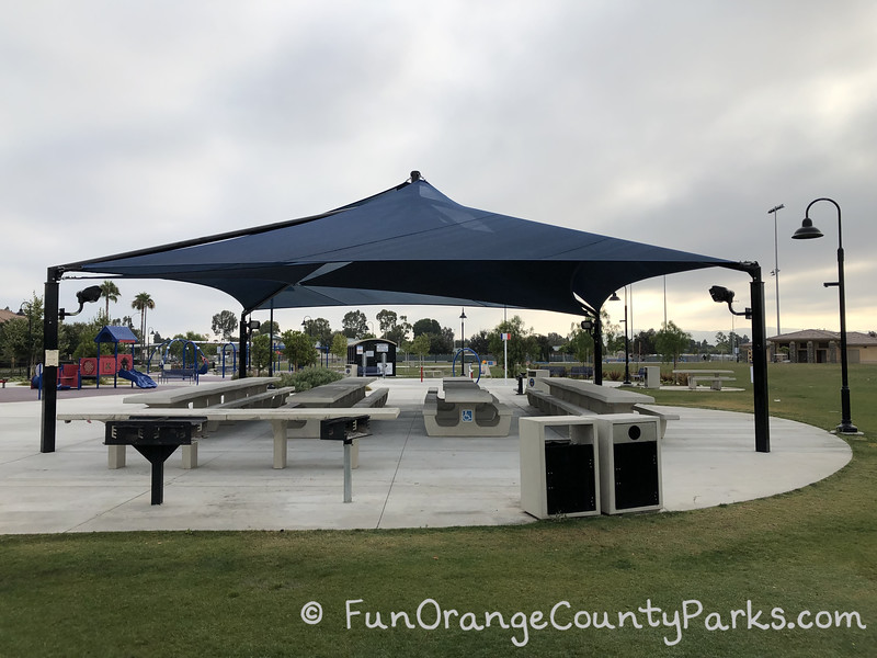 large blue shade structure over concrete picnic tables with grills and trash receptacles in the foreground