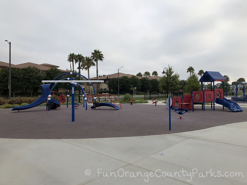 preschool play area at Veterans Sports Park at Tustin Legacy with baby swings, two small play structures, a spinner, and two ride-on toys on a flat recycled rubber surface