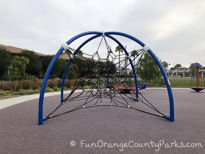 a spiderweb climber play structure with blue metal pipes curved to hold a star shaped black ropes to climb