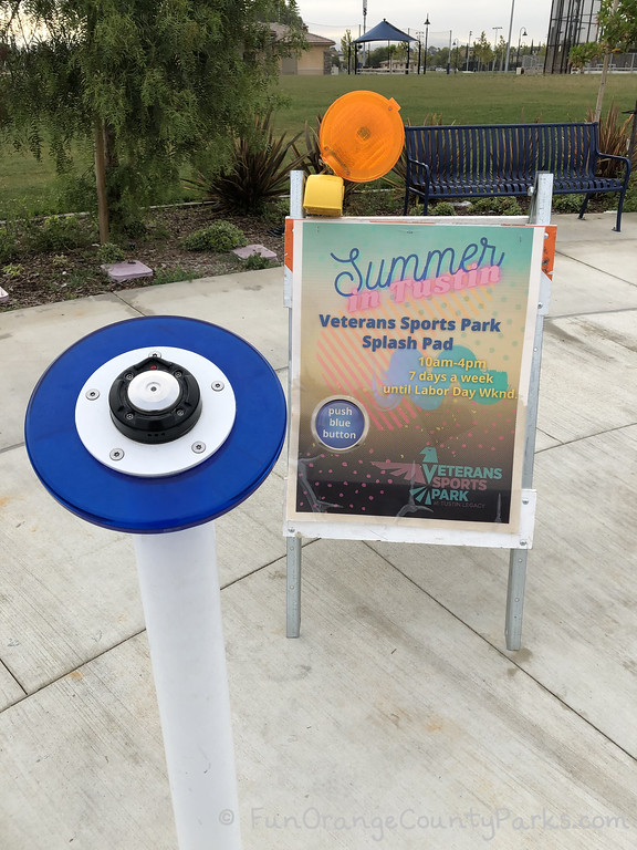 """a pedestal with a blue button about the size of an adult's palm with a sign that says """"Summer in Tustin: Veterans Sports Park Splash Pad 10am-4pm 7 days a week until Labor Day Wknd"""" and a blue circle on the sign that says """"push the blue button"""" along with the Veterans Sports Park logo"""