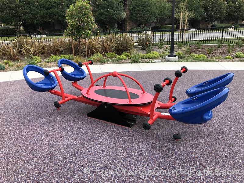 four person teeter-totter with blue seats and red handles very close to the ground