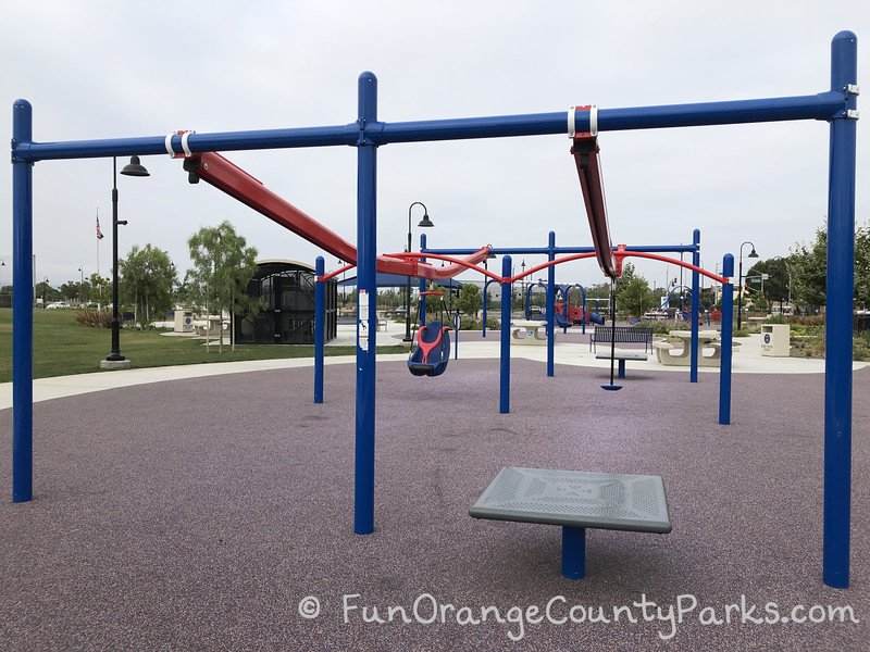view of Veterans Sports Park at Tustin Legacy from the perspective of the zip track with a blue metal structure holding orange metal zip tracks - one with a disc seat and the other with a hanging chair