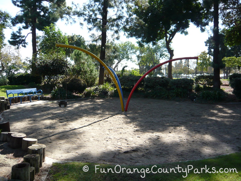 sandy area at Atlantis Play Center in Garden Grove with what looks like 3 bent poles sprouting from the ground with 3 baby swings hanging from the tips of the blue, yellow, and red poles