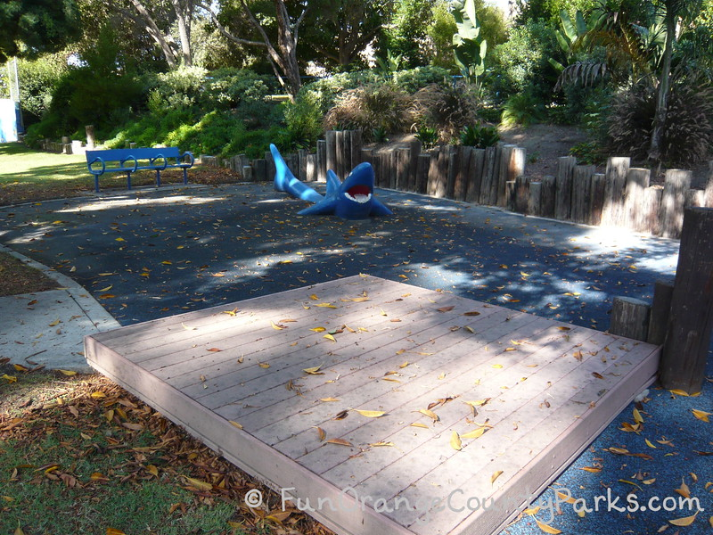 small raised wooden stage in a shady park setting with a blue shark for climbing and a blue bench