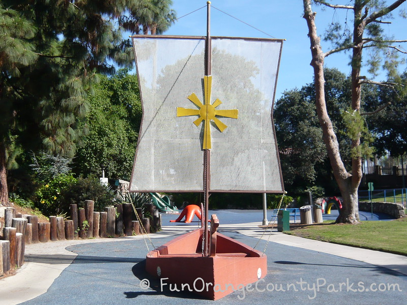 Atlantis Play Center in Garden Grove park setting with a peach colored concrete viking ship and white sail with a yellow star