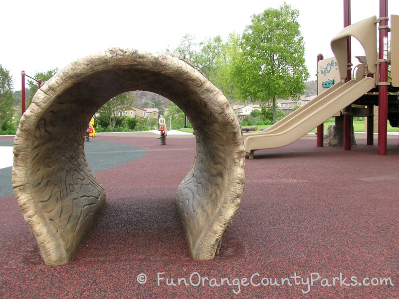 View of Wildcatters Park playground through a log tunnel play structure with slides on the left and spring ride-on toys