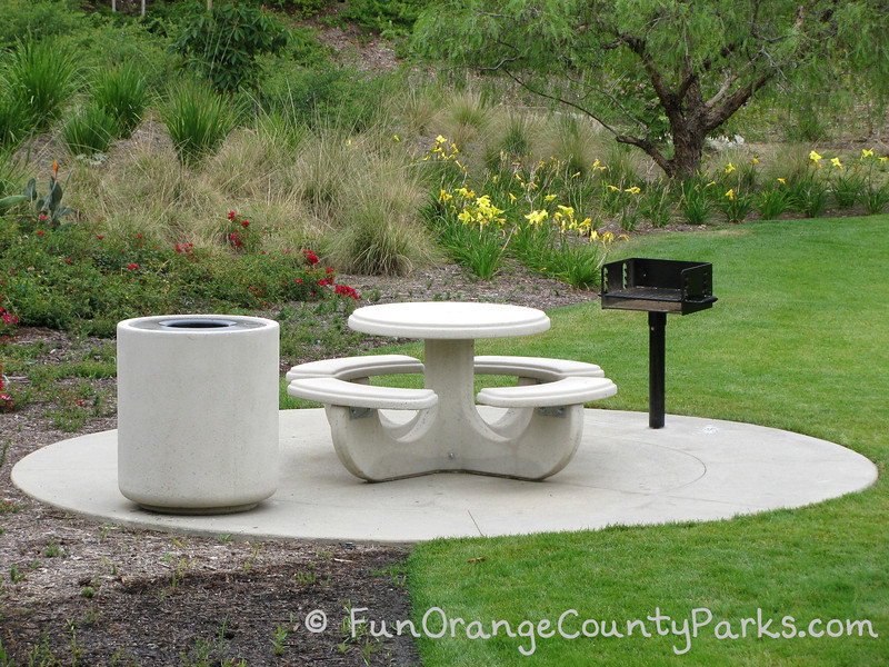 circular concrete picnic table on a concrete pad with a concrete trash receptacle and grill at Wildcatters Park in Brea