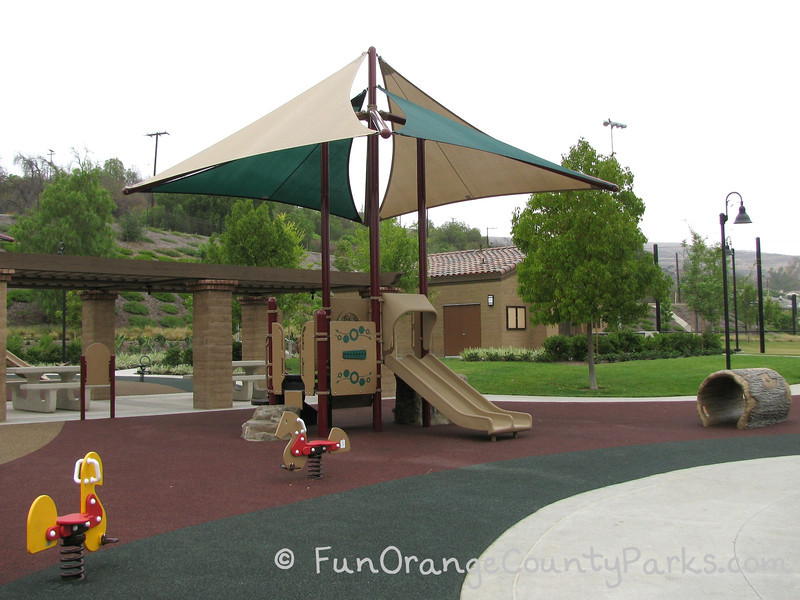 Another playground view of the ride on toys and small playground with a double slide and nearby log tunnel. Covered picnic area behind.