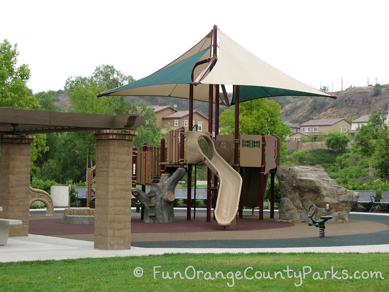 Wildcatters Park in Brea playground with rock for climbing and tree trunk ladder on recycled rubber playground surface. Neighborhood houses in the background.