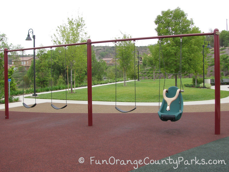 3 bench swings and 1 accessible over red recycled rubber with park setting in the background with lawn and trees